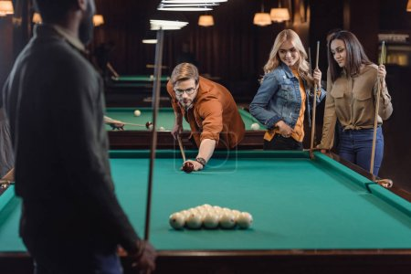 young multiethnic friends playing in pool at bar
