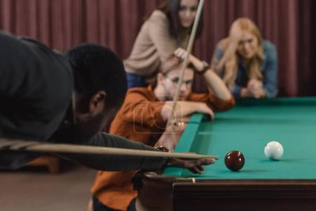 young african american man playing in pool at bar with friends