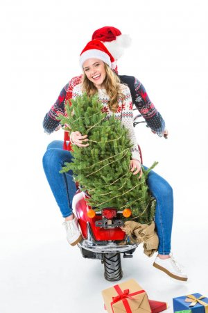 smiling couple with christmas tree riding scooter, scattered presents lying down, isolated on white