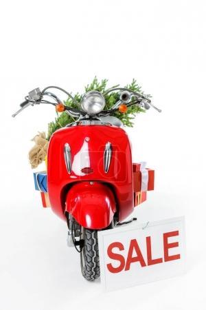 Foto de Árbol de Navidad y regalos en vespa rojo con signo de venta, aislado en blanco - Imagen libre de derechos