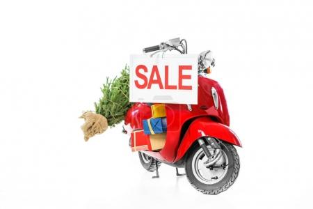 Photo for Christmas tree and presents on red scooter with sale sign, isolated on white - Royalty Free Image