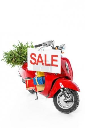 christmas tree and gift boxes on red scooter with sale sign, isolated on white