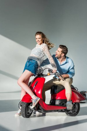 cheerful young couple posing near red scooter together