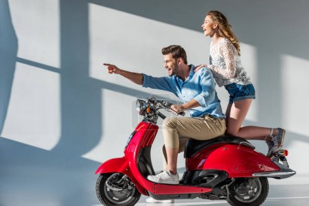 side view of smiling man pointing away while sitting on scooter together with girlfriend