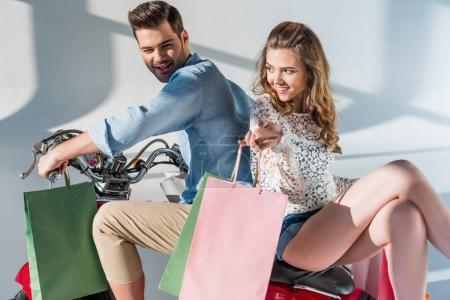 Photo for Stylish couple in love with shopping bags sitting on red scooter - Royalty Free Image