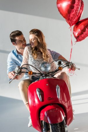 Photo for Couple with red heart shaped balloons riding red scooter together - Royalty Free Image