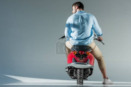 back view of fashionable man in shirt sitting on red scooter