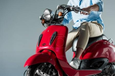 partial view of man in stylish clothing sitting on red scooter