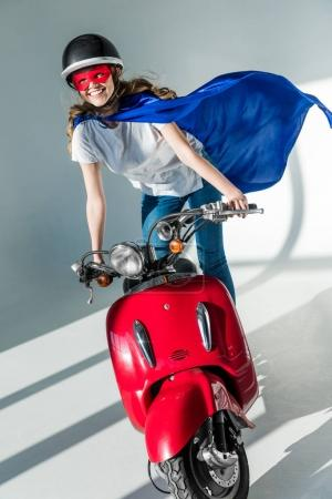 happy woman in superhero costume and protective helmet on red scooter
