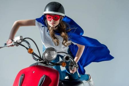 Photo pour Portrait de femme en costume de super-héros et casque de protection sur scooter rouge - image libre de droit
