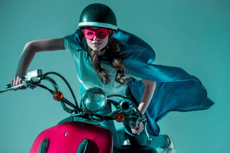 portrait of woman in superhero costume and protective helmet riding red scooter