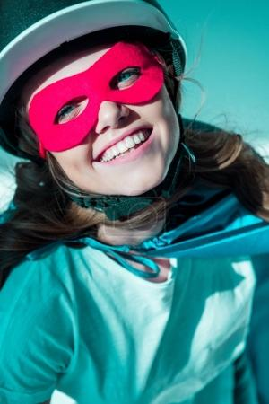 Photo pour Portrait de femme gaie dans le casque, masque de super-héros et cape regardant la caméra - image libre de droit