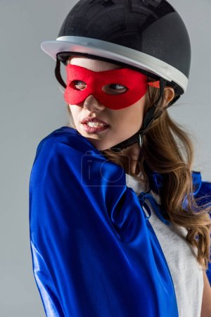 portrait of thoughtful woman in helmet, superhero mask and cape looking away