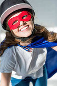 portrait of cheerful woman in helmet, superhero mask and cape looking at camera