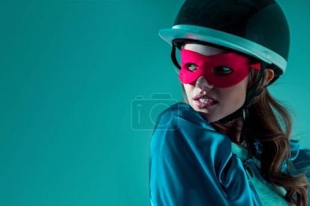 Photo pour Portrait de femme réfléchie en casque, masque de super-héros et cape détournant les yeux - image libre de droit