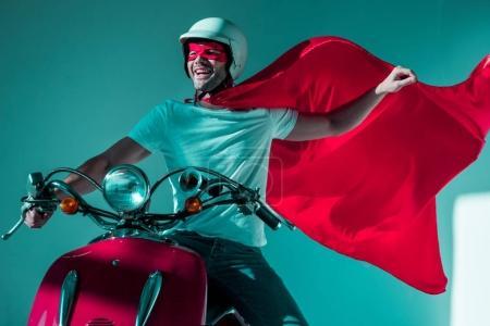 Photo pour Portrait de l'homme heureux en casque de protection et costume de super-héros scooter rouge - image libre de droit