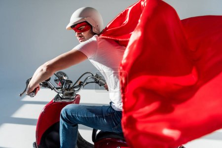 side view of man in protective helmet and superhero costume on red scooter