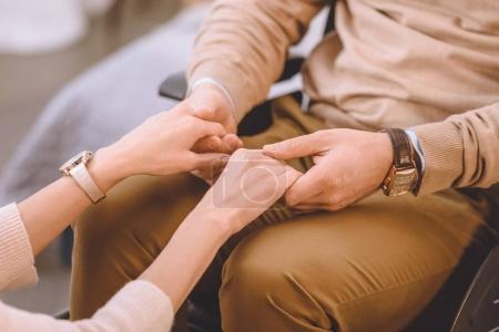 Foto de Imagen recortada de marido en silla de ruedas y esposa de la mano - Imagen libre de derechos