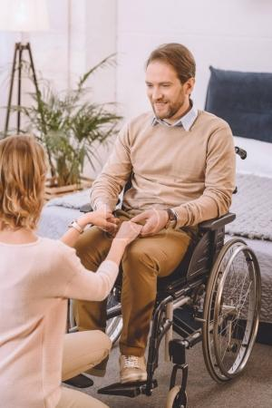 Photo for Happy husband on wheelchair and wife holding hands - Royalty Free Image