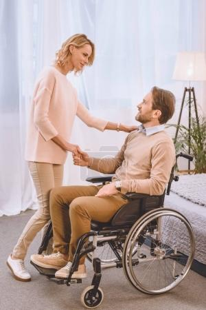happy husband on wheelchair and wife holding hands in bedroom