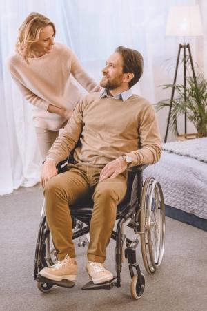 Photo for Happy husband on wheelchair and wife looking at each other - Royalty Free Image