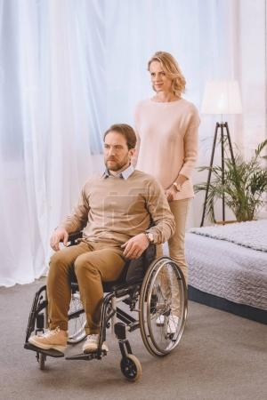Photo for Husband on wheelchair and wife looking away in bedroom - Royalty Free Image