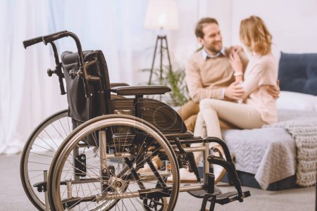 happy husband with disability and wife sitting and hugging on bed with wheelchair on foreground