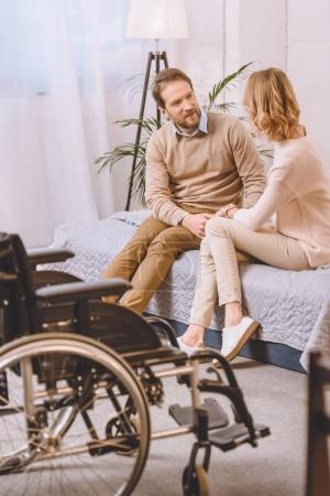 husband with disability and wife sitting and talking on bed
