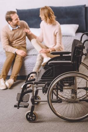 husband with disability and wife sitting and talking on bed with wheelchair on foreground