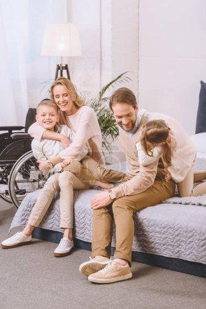 Photo pour Père souriant avec handicap et mère jouant avec les enfants sur lit - image libre de droit