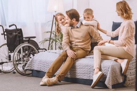 happy father with disability and mother sitting with kids on bed