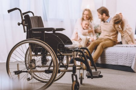 Photo for Happy father with disability and mother sitting with children on bed with wheelchair on foreground - Royalty Free Image