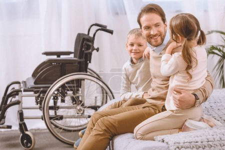 happy father with disability sitting with children on bed