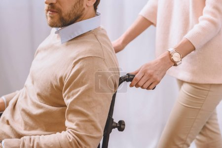 cropped image of wife carrying husband in wheelchair