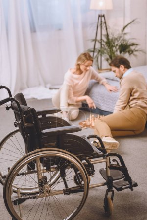 husband with disability and wife playing chess in bedroom with wheelchair on foreground
