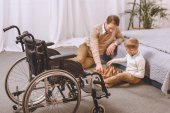 father with disability and son playing chess on a floor with wheelchair on foreground