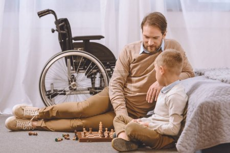 father with disability and son playing chess on a floor