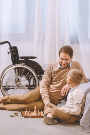 father with disability and son playing chess