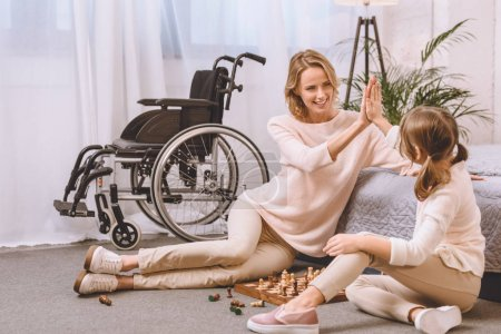 mother with disability and daughter playing chess and giving high five