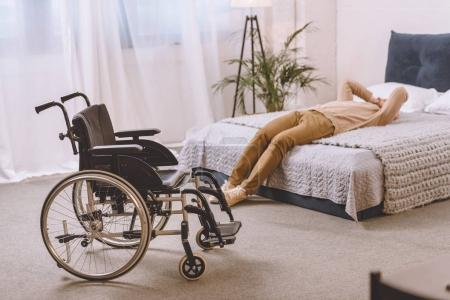 upset man with disability lying on bed in bedroom