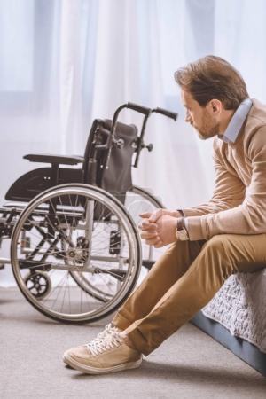 Photo pour Homme inquiet avec handicap assis sur le lit et regardant en fauteuil roulant - image libre de droit