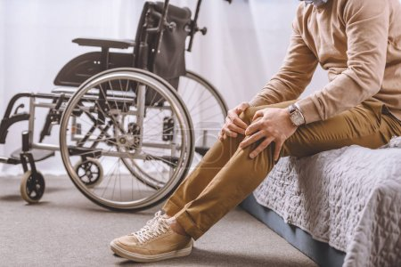 Photo for Cropped image of man with disability sitting on bed and touching legs - Royalty Free Image