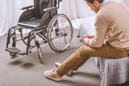 Photo pour Homme triste handicapée assise sur le lit, fauteuil, debout près de - image libre de droit