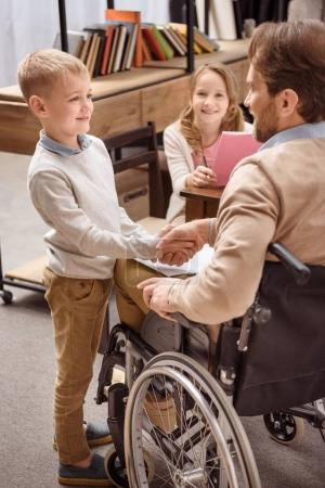 father on wheelchair and smiling son shaking hands