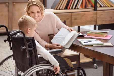 happy mother showing something in book to son on wheelchair
