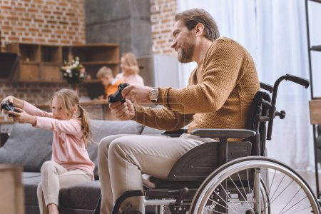 Photo for Happy daughter and father on wheelchair playing video game with joysticks - Royalty Free Image