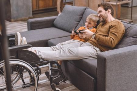 Photo for Happy father and son playing video game with game pads - Royalty Free Image