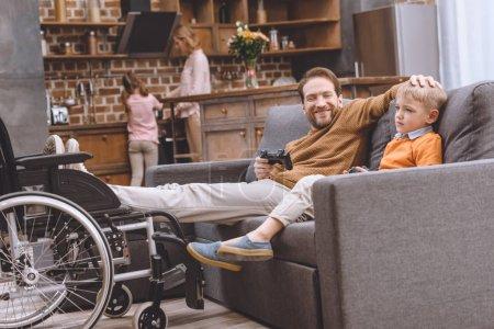 heureux père handicapé avec les jambes sur fauteuil roulant et mignon petit fils jouer avec joysticks ensemble à la maison