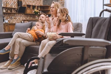 close-up view of wheelchair and family sitting on sofa and eating popcorn behind