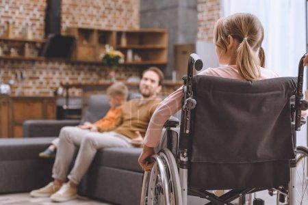 arrière de l'enfant handicapé assis en fauteuil roulant et en regardant père et son frère assis sur le canapé à la maison